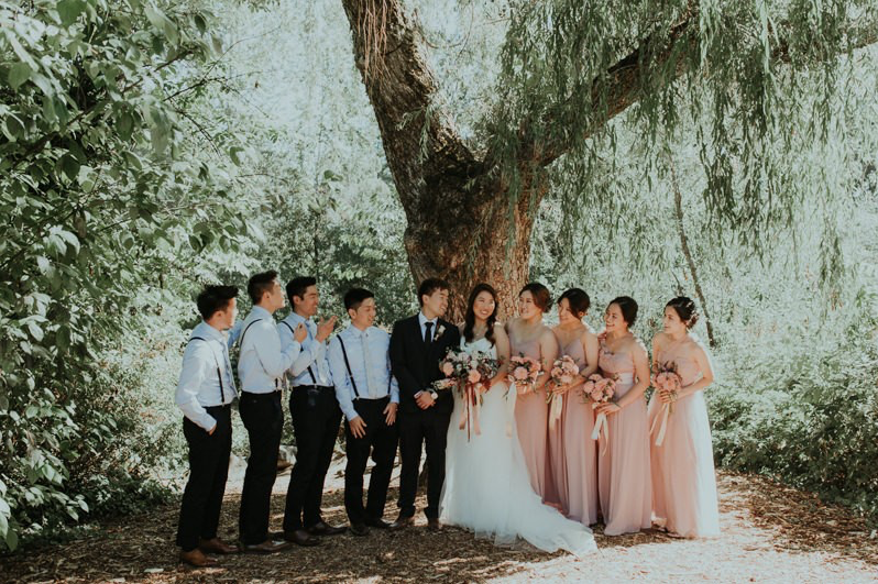 A wedding couple and their bridesmaids and groomsmen are standing next to a big tree at Robinswood House.