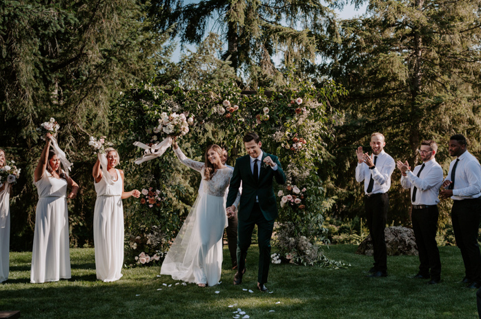 A wedding couple and their bridesmaids and groomsmen are cheering and standing at the Trinity Tree Farm.