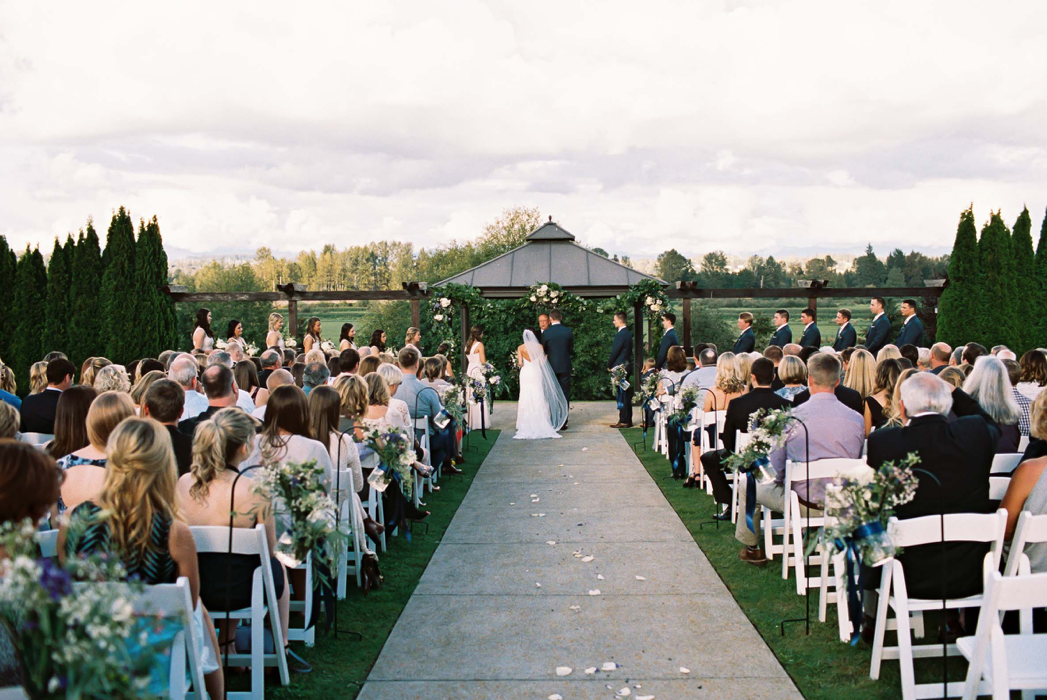 A wedding couple is standing at the end of the aisle with their wedding guests next to the aisle.