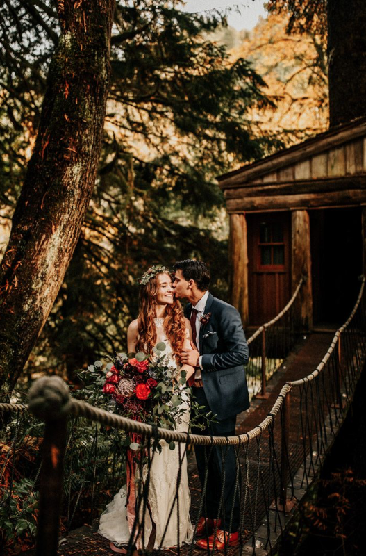 A wedding couple is standing on a bridge, in front of Treehouse Point.