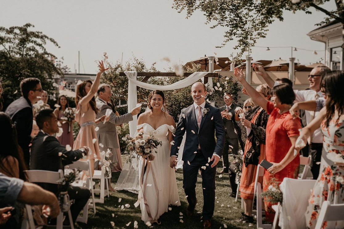 A wedding couple is walking down the aisle hat their guests are cheering.