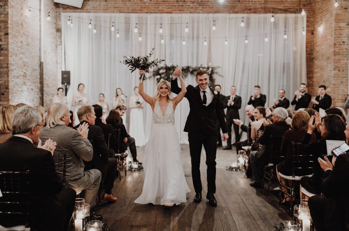 A wedding couple is walking down the aisle and their guests are cheering.