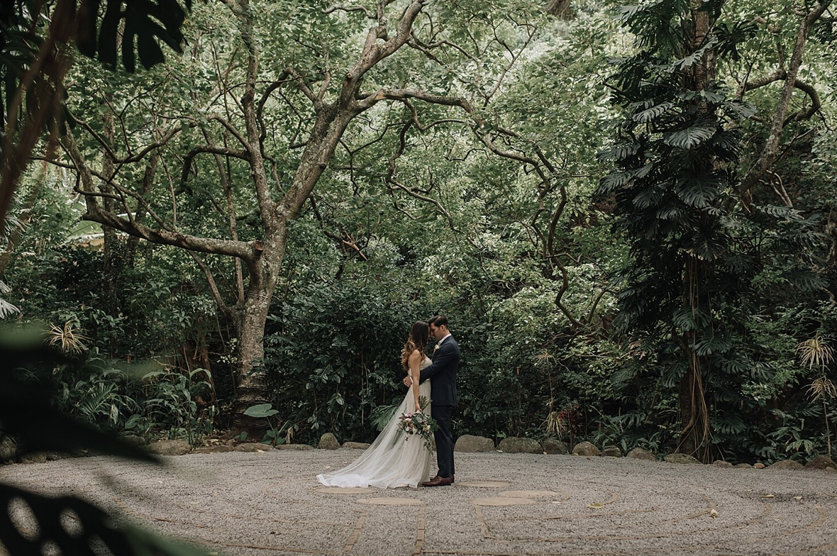 A wedding couple is holding each other at the Sacred Garden of Maliko in Makawao, Hawaii.