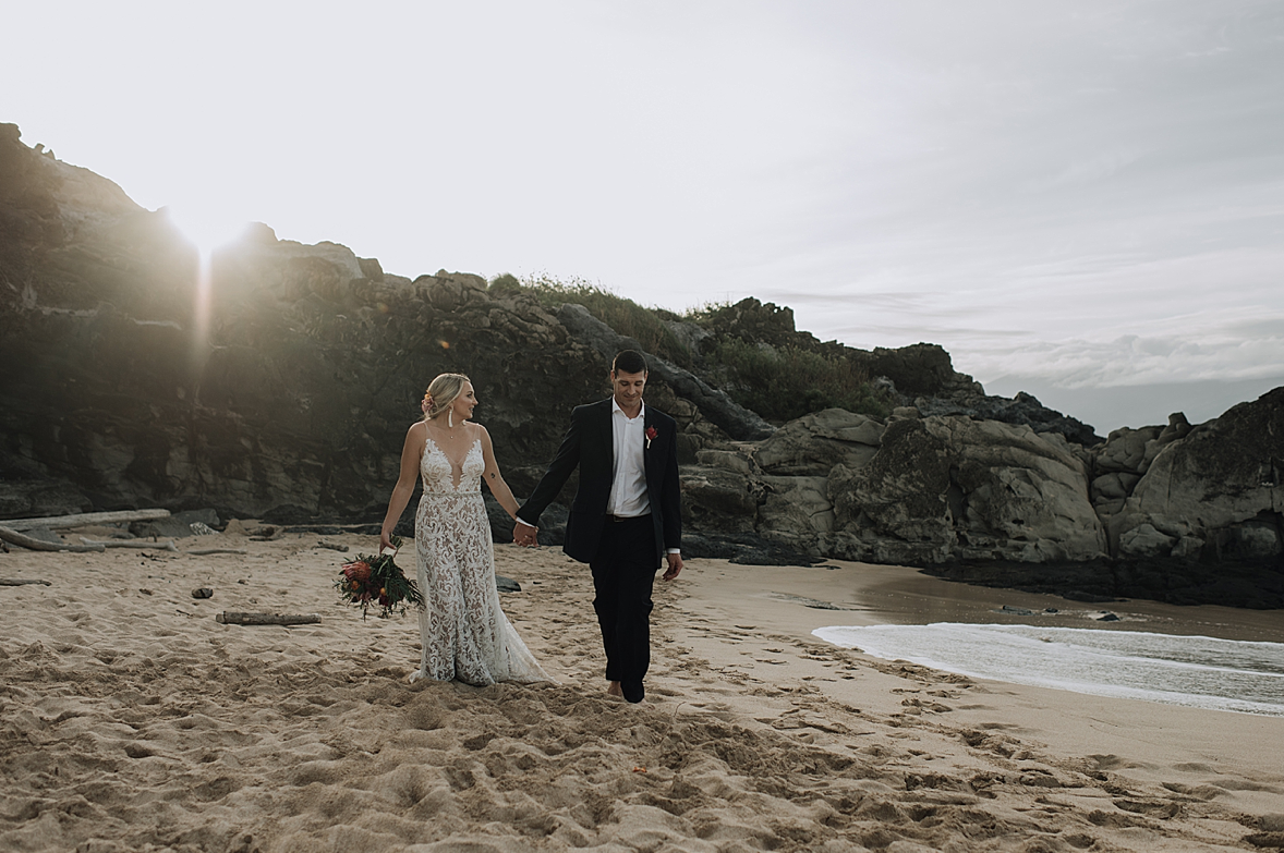 A wedding couple is holding hands and walking along the Ironwoods Beach in Maui, Hawaii.