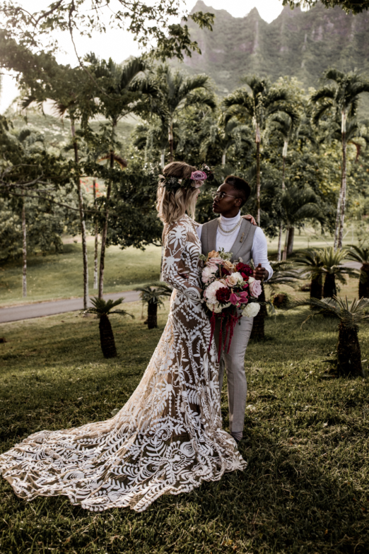 A wedding couple is holding each other and standing at the Moli´i Gardens.