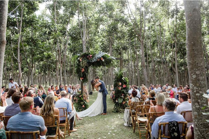 A wedding couple is kissing each other at the end of the aisle, at the Botanical Garden in Kauai.