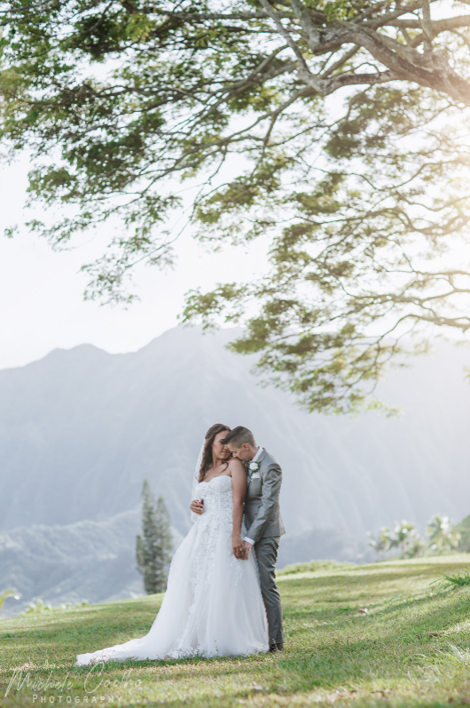 A wedding couple is holding each other at the He'eia State Park.
