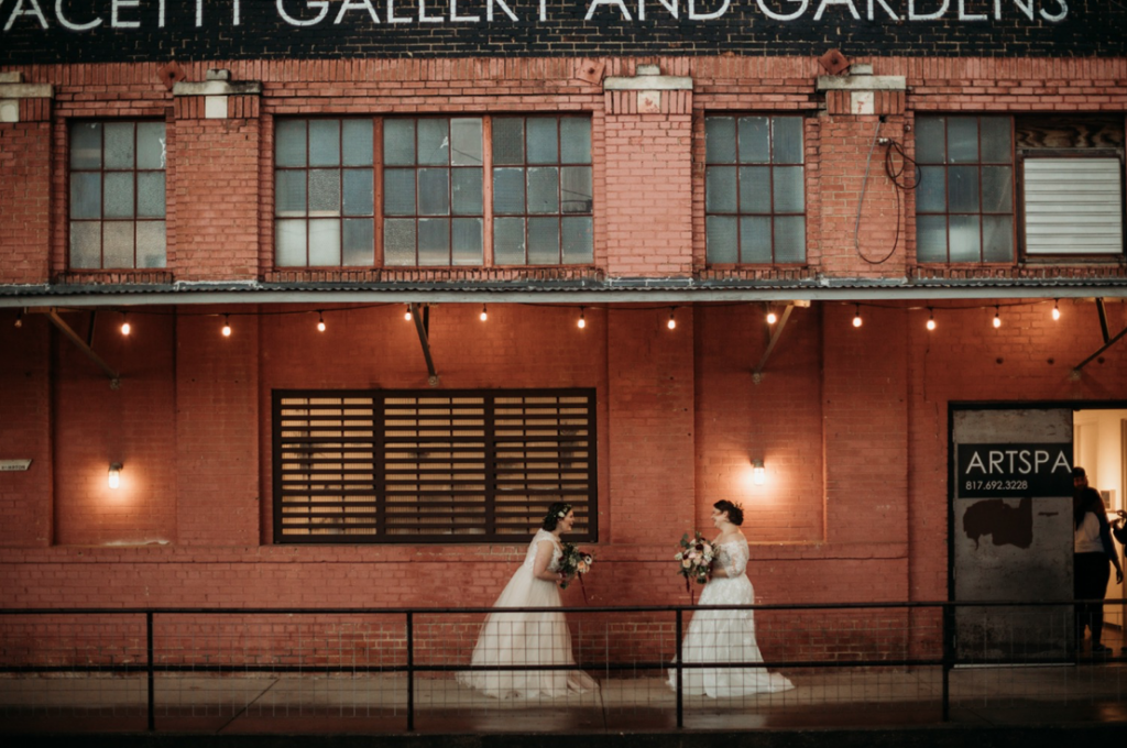 A wedding couple is standing in front of a brick wall at the LGBTQ friendly Artspace 111 Gallery and Gardens, one of the wedding venues in Texas.