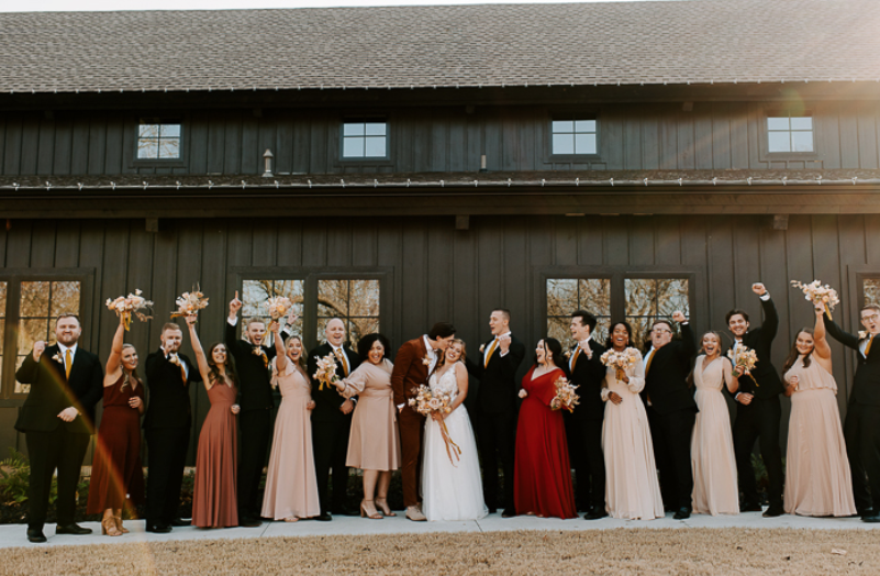 A wedding couple and their bridesmaids and groomsmen are standing in front of the Spain Ranch, one of the wedding venues in Oklahoma.