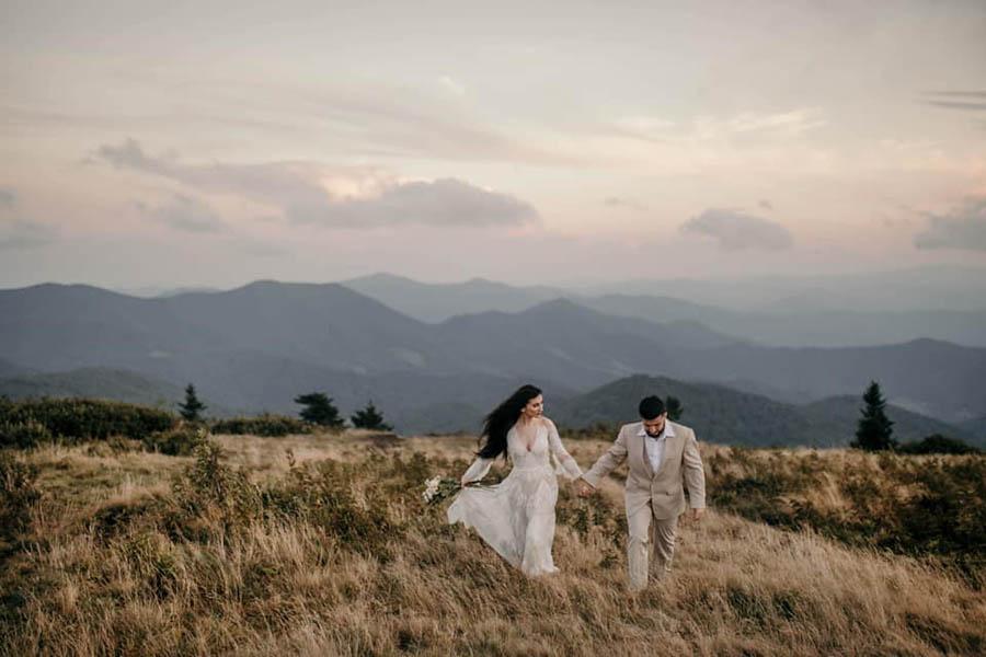 A wedding couple is walking in a meadow.