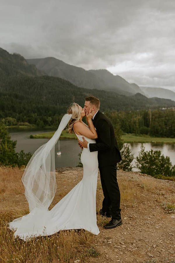 A wedding couple is kissing at the Columbia Gorge in Oregon.