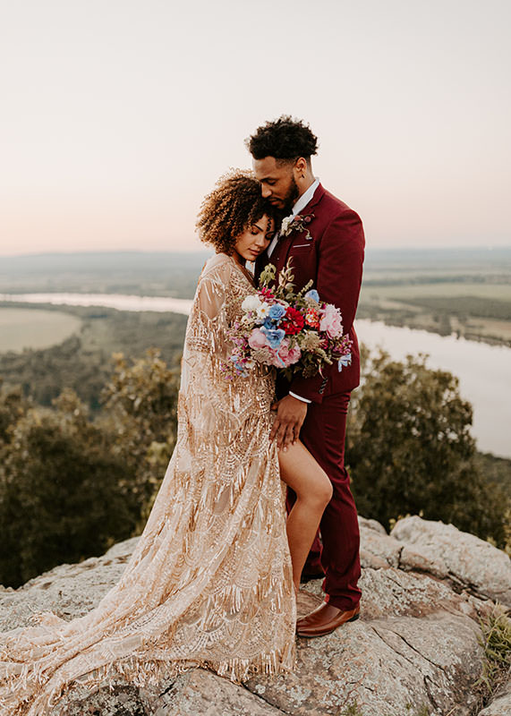 A wedding couple is standing on top of a mountain and is holding each other.