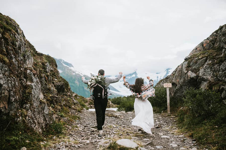 A wedding couple is hiking through the mountains.
