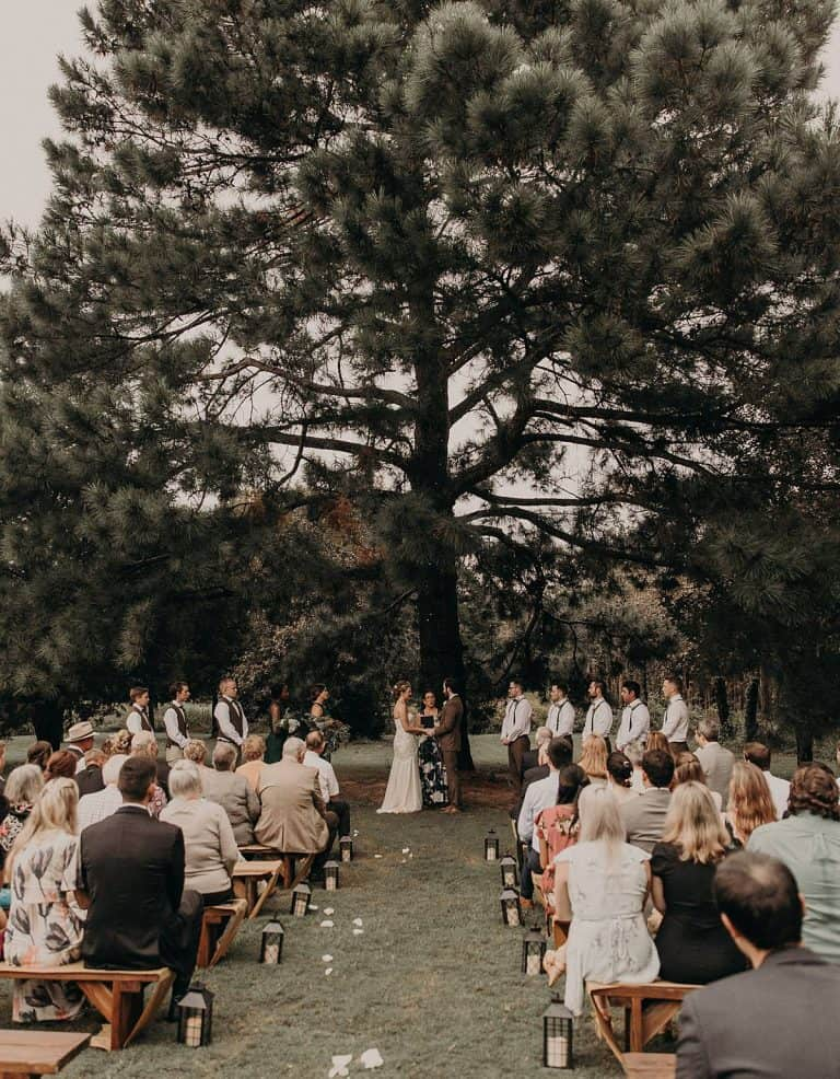 A wedding couple is getting married next to their wedding guests and they are standing in front of a big tree, at one of the wedding venues in Texas. at the Homestead at Old Potato Road.