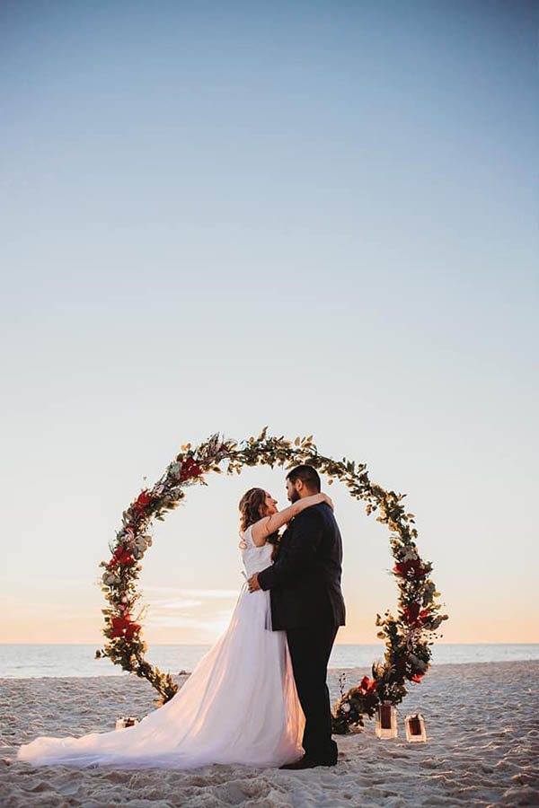 A wedding couple is holding each other and standing at the beach.