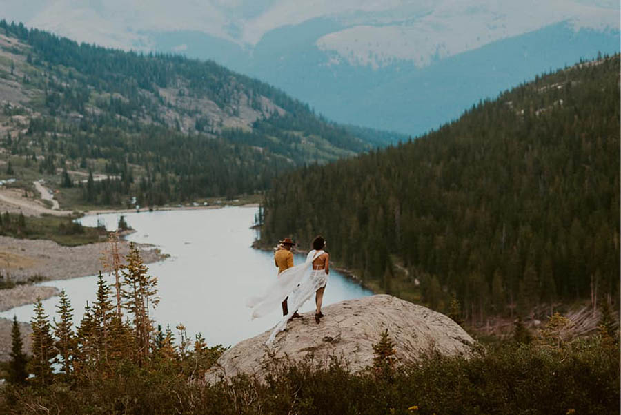 A wedding couple is standing on a rock in the mountains.