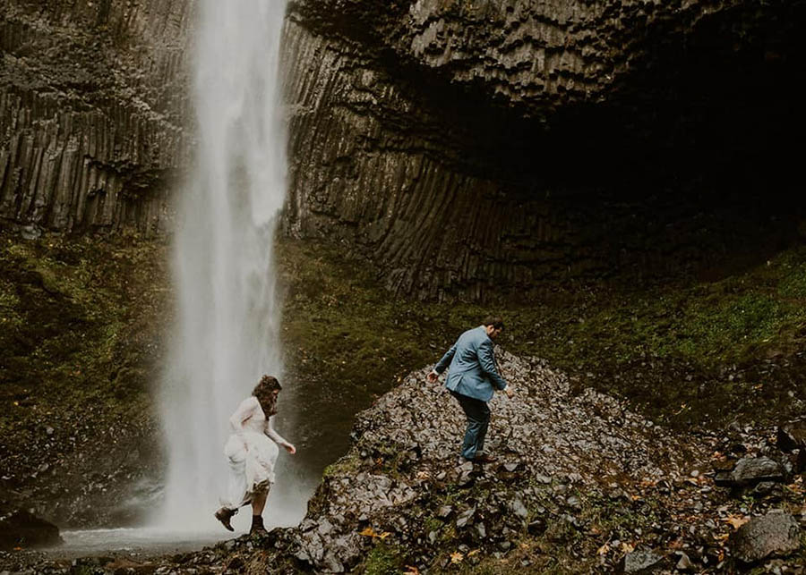 A wedding couple is hiking next to the Latourell Falls in Oregon.