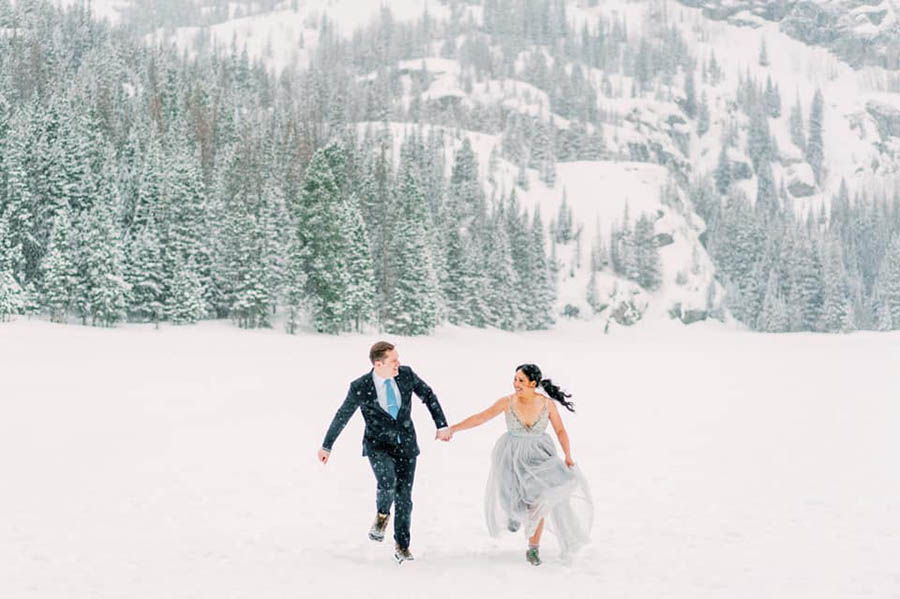 A wedding couple is holding hands and running through the snow.