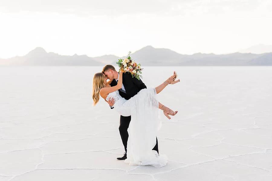 A groom is holding his bride at the Bonneville Salt Slats in Utah.