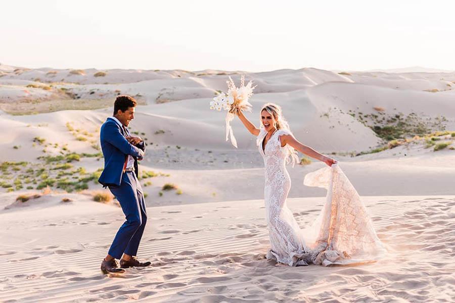 A wedding couple is dancing on the Sand Dunes in Utah, one of the wedding venues in Utah.
