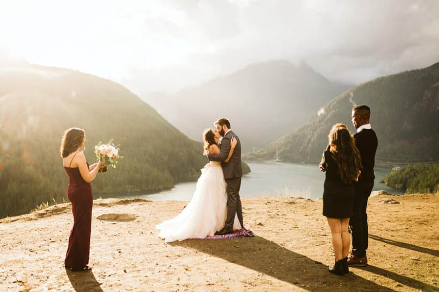 A wedding couple is kissing each other and and three wedding guests are standing next to them at the North Cascades National Park in Washington.