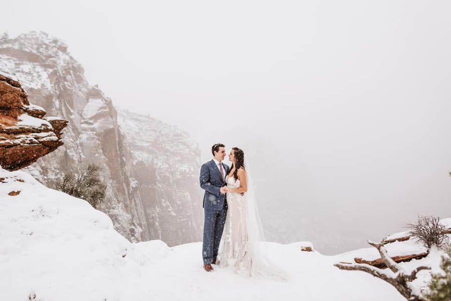 A wedding couple is holding each other and standing in a snowy part of the mountains at the Zion National Park.