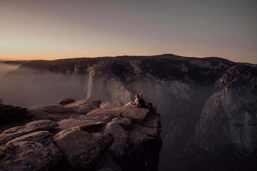 A wedding couple is sitting on the edge of a mountain at Yosemite National Park.