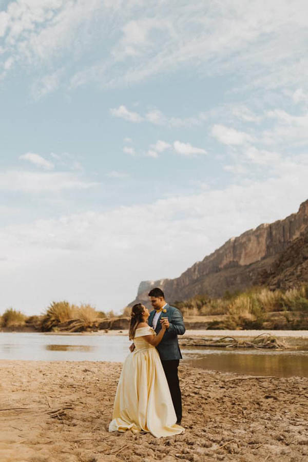 A wedding couple is standing holding each other and standing next to the Big bend in Texas.