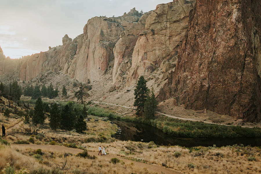 A wedding couple is walking through a valley at the Smith Rockey State Park in Oregon.