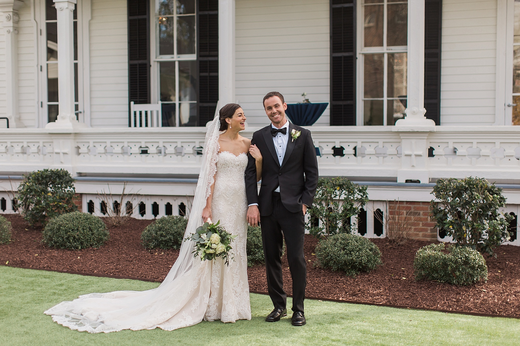 A wedding couple is standing in front of the Merrimon-Wynne House in North Carolina.