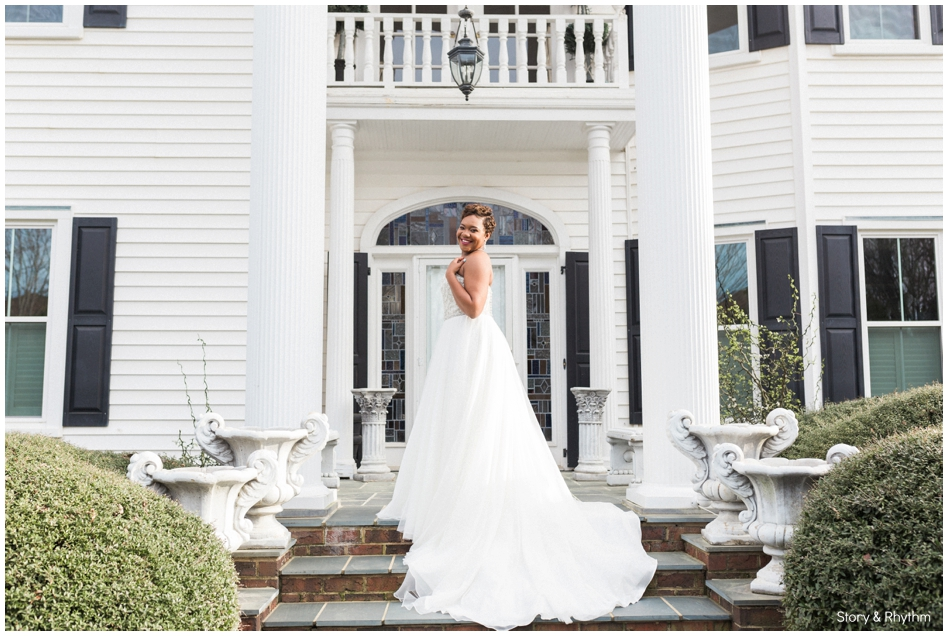 A bride is standing in front of the Matthews House in North Carolina.