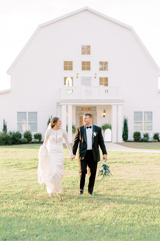 A wedding couple is holding hands and walking in front of the Harvest Hollow Barn in Alabama.