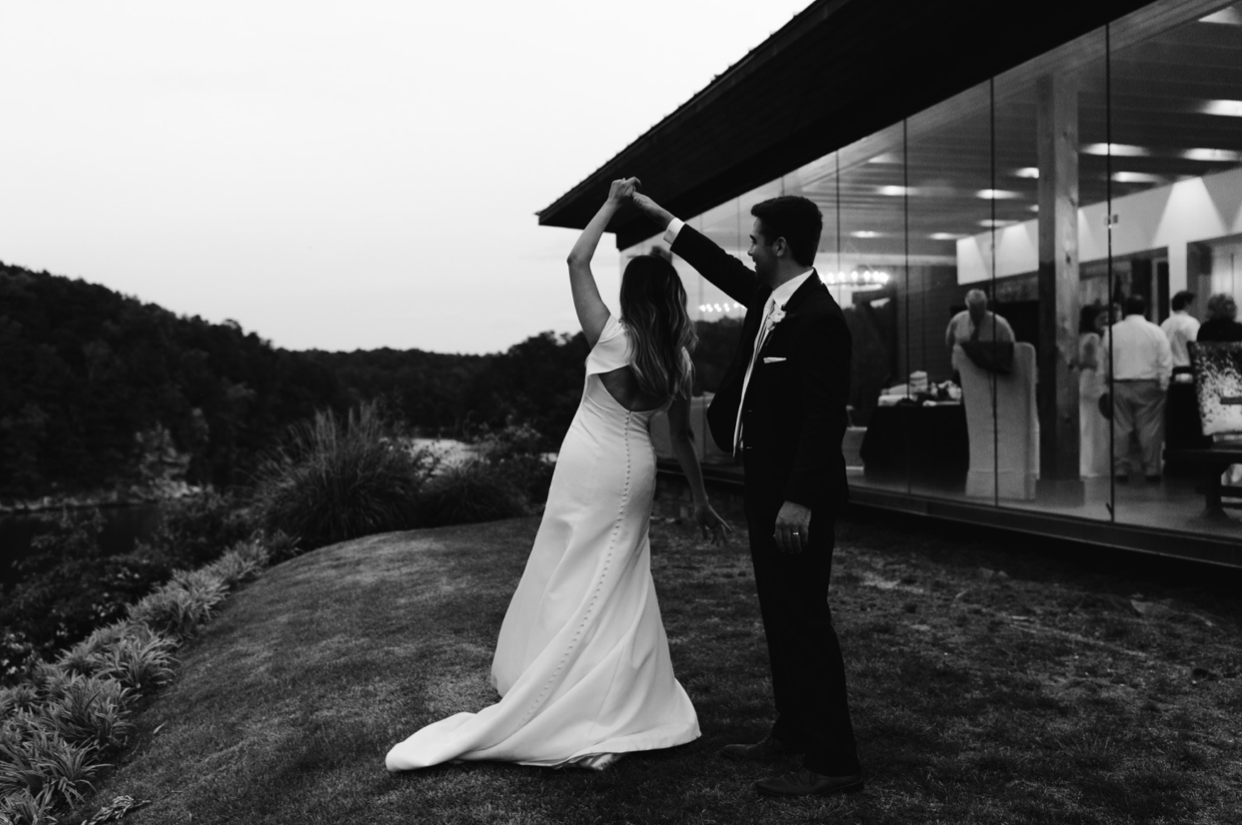 A wedding couple is dancing outdoes the Glass House in Alabama.