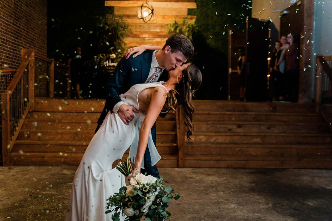 A wedding couple is kissing each other path the Loft 212, one of the wedding venues in Alabama.