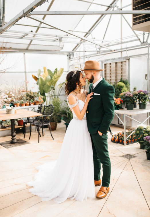 A wedding couple is standing in a greenhouse at the Market at Grelen in Virginia.