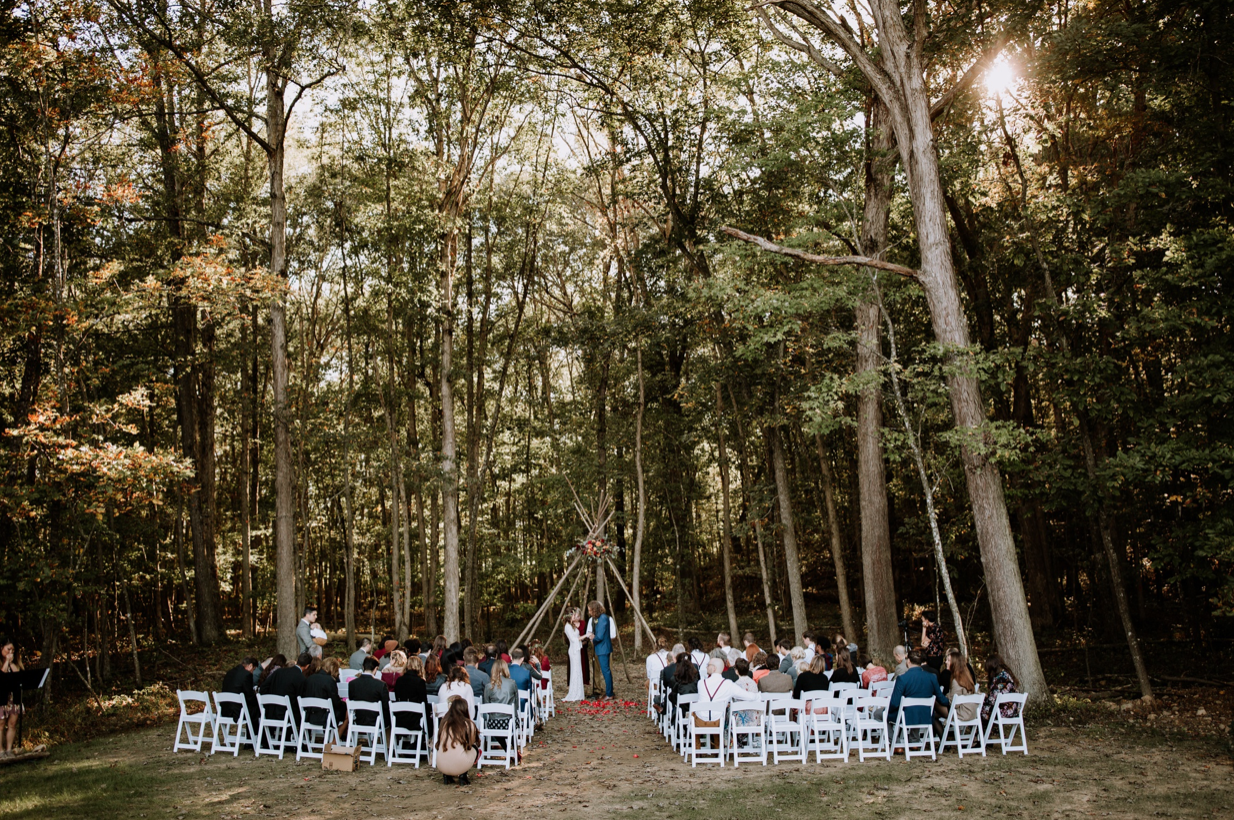 A wedding couple is getting married in a forest at Brenwood Lake Weddings, one of the wedding venues in Virginia.