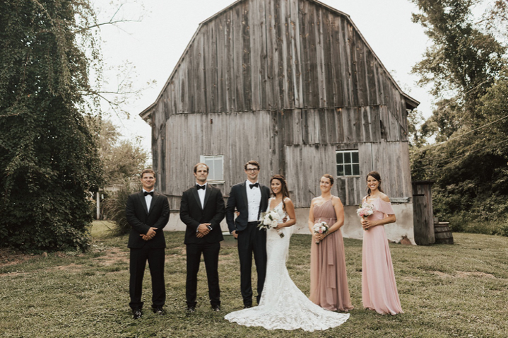 A wedding couple and their bridesmaids and groomsmen are standing on front of a barn at the Barns at Hamilton Station Vineyards in Virginia.