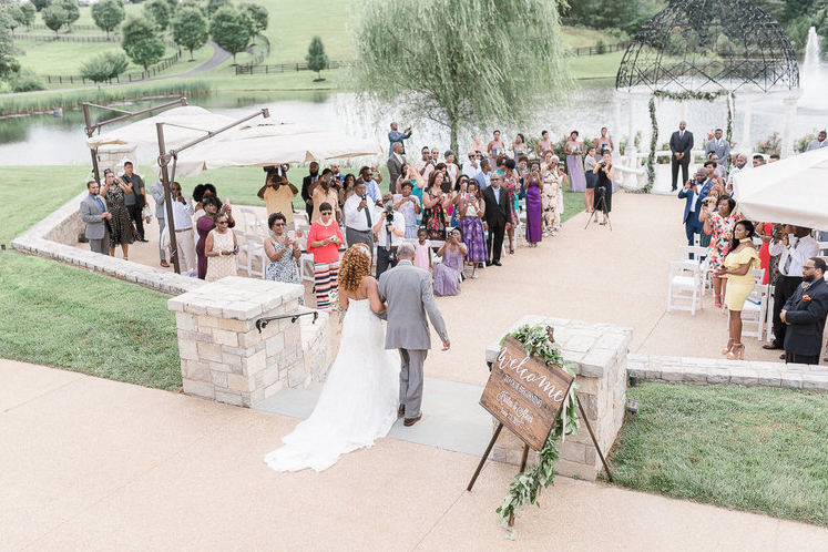 A bride and her father are walking down the aisle at the Mount Ida Farm in Charlottesville, Virginia.
