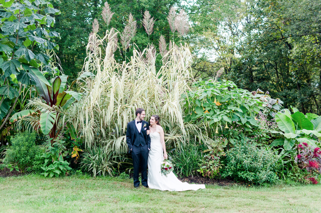 A wedding couple is standing in the Atrium at Meadowlark Botanical Gardens in Virginia.