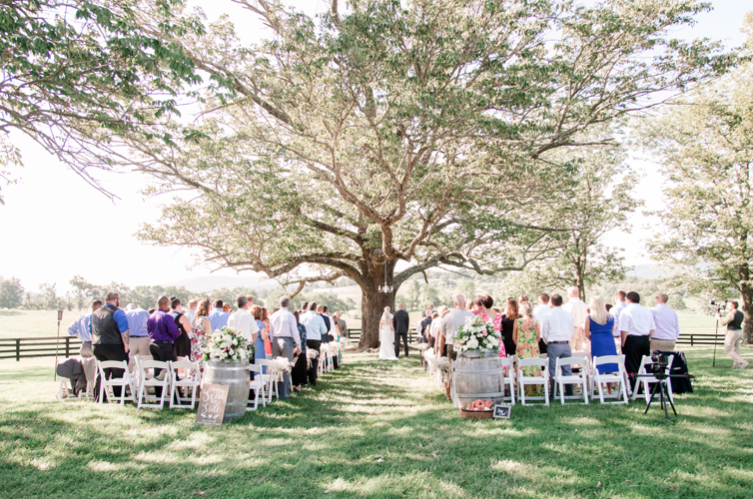 A wedding couple is getting married next to a big tree at The Marriott Ranch, in Virginia.