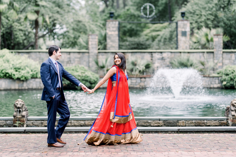 An engaged couple is holding hands and walking through the Norfolk botanical garden in Virginia.