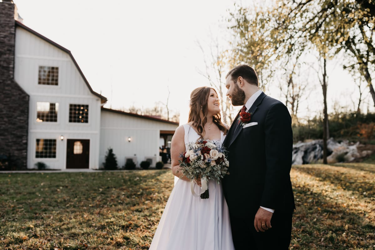 A wedding couple is holding hands, looking at each other and standing in front of the Historic Rosemont Springs in Virginia.