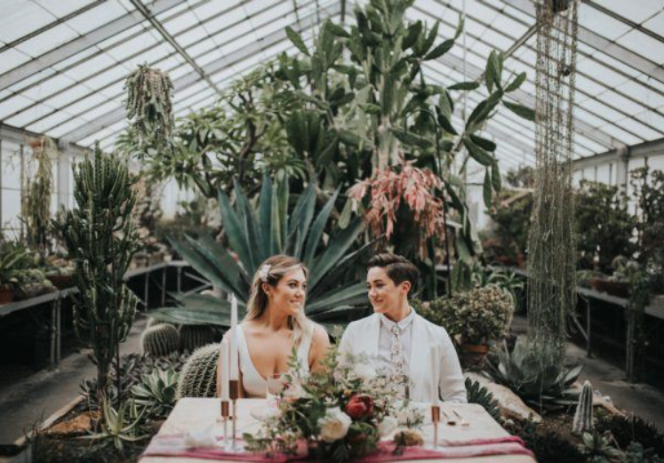 A wedding couple is sitting at a table in a green house at Kingwood Center Gardens. one of the wedding venues in Ohio.