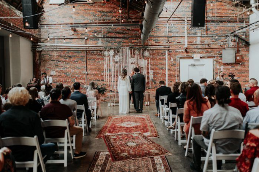 A wedding couple is getting married in front of a brick wall at Strongwater Columbus, Ohio.