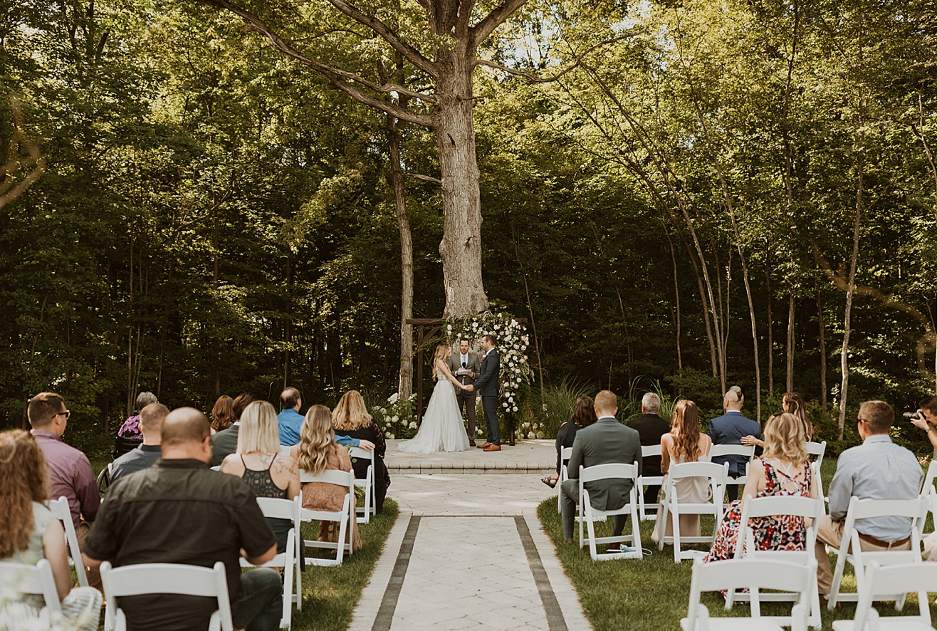 A wedding couple is getting married in front of a big tree at Crimson Lane, in Ohio.