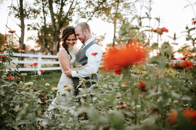A wedding couple is holding each other and is standing behind flowers at the Marmalade Lily in Ohio.