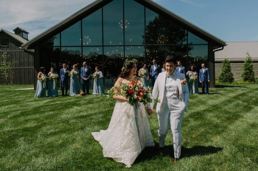 A wedding couple is walking across the lawn and holding hands at the Jorgensen Farms in Ohio.