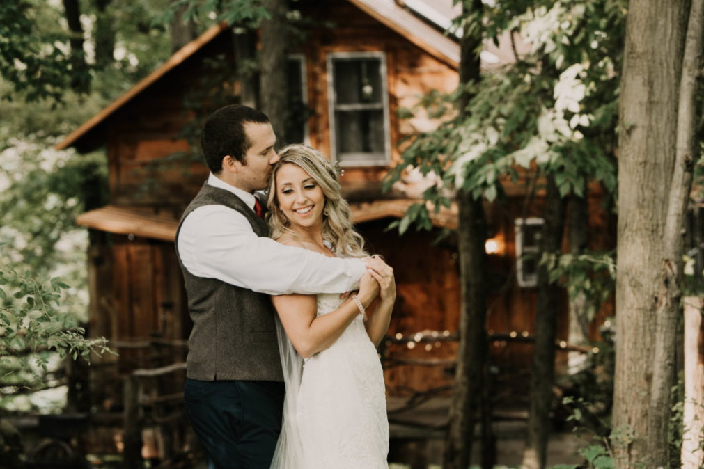 A wedding couple is holding each other at the Mohicans Treehouse Resort in Ohio.
