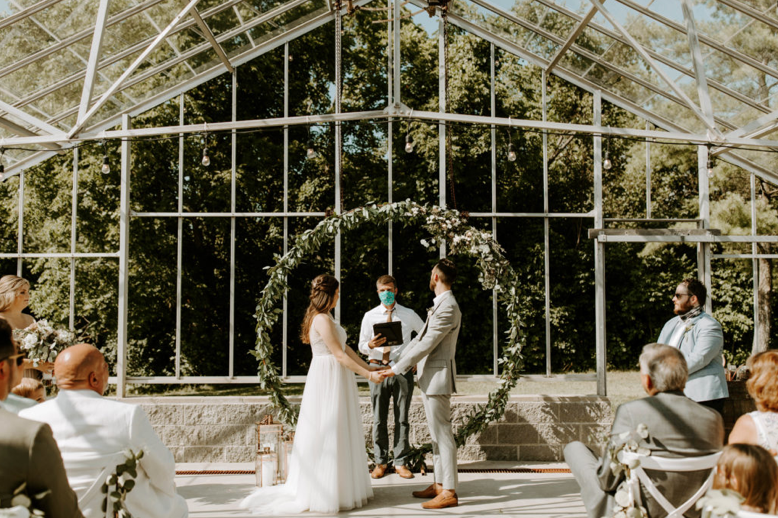 A wedding couple is getting married in a greenhouse at the Alum Creek Farm in Ohio.