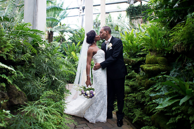 A wedding couple is kissing each other at the Garfield Park Conservatory in Illinois.